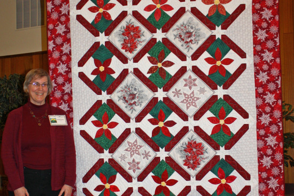 Anna Leonard designed the poinsettia blocks for BBQ's Nov. Block of the Month.  As the winner, Barbara Smith added some pre-printed Christmas blocks, sashing and setting triangles.  Barbara quilted this also.  The yellow button centers were crocheted by Anna's daughter.