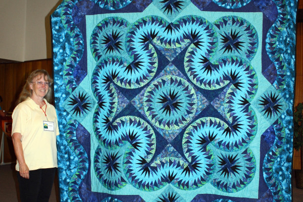 """Celtic Wave"" was created & quilted by Pat Kluckhohn as her second try at paper piecing.  She hand-quilted this for her son & daughter-in-law's 10th anniversary."