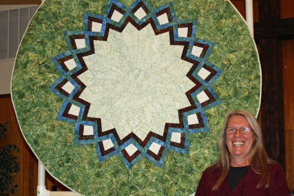 "Sharon Beidler pieced ""Merry Christmas Go Round"" for her daughter-in-law.  Jami Herndon was the quilter.  The pattern is from 'Quilts without Corners'."