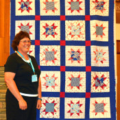"This ""Quilt of Honor"" from Fons & Porter was made by Maryon Evans and quilted by Connie Emmen for the female Veterans presentation at the Quilt Show."