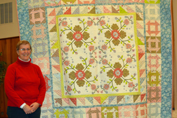 """Barbara Smith made and quilted """"Churn Dash Garden"""" for the Pink Hippo ladies.  The center is appliqued and the churn dash blocks were cut on her Go Cutter.  This speeds up the process and accuracy!"""