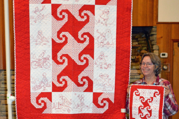 """Margie Braach hand embroidered and quilted """"Redwork Kids"""".  The miniature quilt is made with what was supposed to be the corner stones!"""