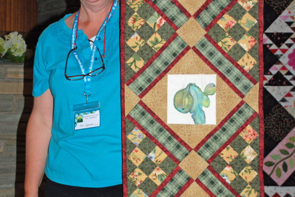 "Ann Swanson created & quilted ""Fruit for Lunch"", from painted blocks made by her sister for the Guild Challenge.  Ann used the Lucky at Checkers pattern for the table runner."