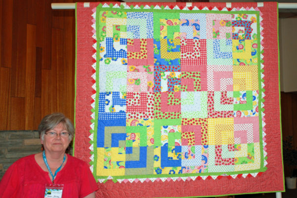 """Berry Bouquet"" was made by Karen Falvey & quilted by Jami Herndon.  The pattern is a kit using the quarter log cabin."