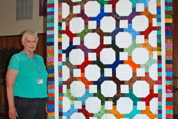 """Blooming Snowball"" was created by Kenna Worthington and quilted by Quilt Expressions.  She made this quilt to try a new Accuquilt die."
