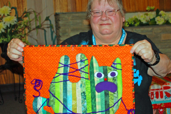 "Leona Manke planned this story quilt, ""Ooops!"" to show how her cats entertain her. She also quilted it herself."