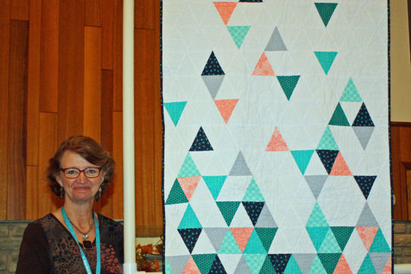 """Cheryl Neruda created and quilted """"Tumbling Triangles"""" for a new niece in Iowa.  The idea came from seeing modern quilts on Pinterest."""