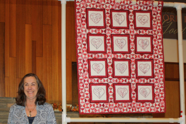 """Madeleine Trainor created & quilted """"La Fleur Au Coeur"""" from 'Redwork in the Garden patterns, which were offered as a BOM several years ago."""
