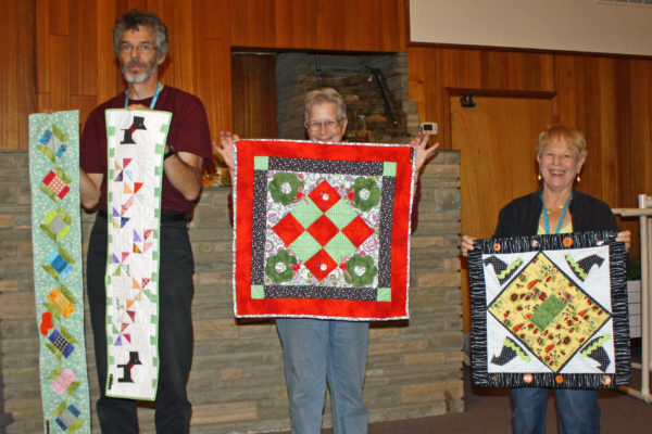Marie Lee created & quilted 4 wall hangings from a Row by Row by Kimber Bell.  Marie is standing on the right.