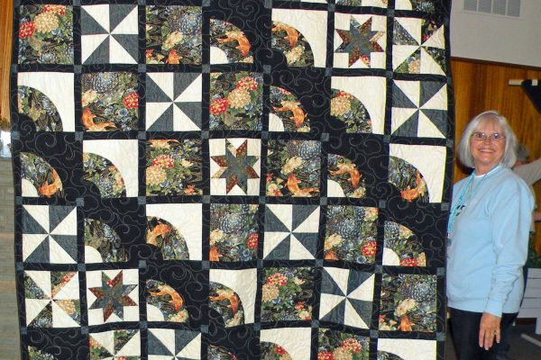 """""""The Dollinger Quilt"""" was pieced by Maggie for her Mom, but was too small for the bed.  Connie Emmen quilted it using lovely Asian fabric for the back."""