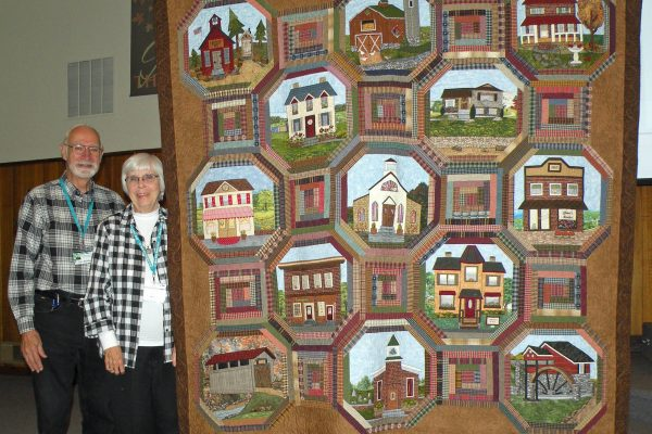 """""""Country Village"""" was created by Dona Mumford & quilted by Yvette Ebaugh.  Donna used patterns from the Quilters Runway and her own designs to make a ribbon winner as the annual BBQ Quilt Show."""