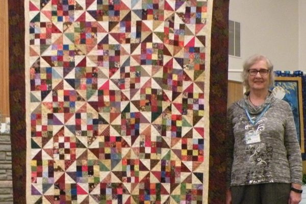 "Jackie Fuller created & quilted ""Scrap Patch Paddlewheel"" with alternating pinwheel blocks by Lynette Jensen."
