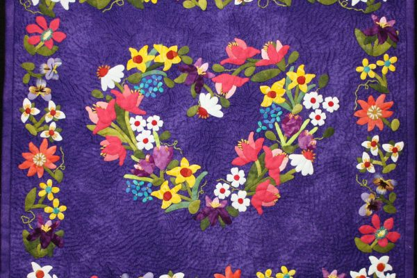 "1st Place - ""Spring Flower Heart"" by Janae Bissinger; hand quilted and recipient of the NACQJ Award of Merit."
