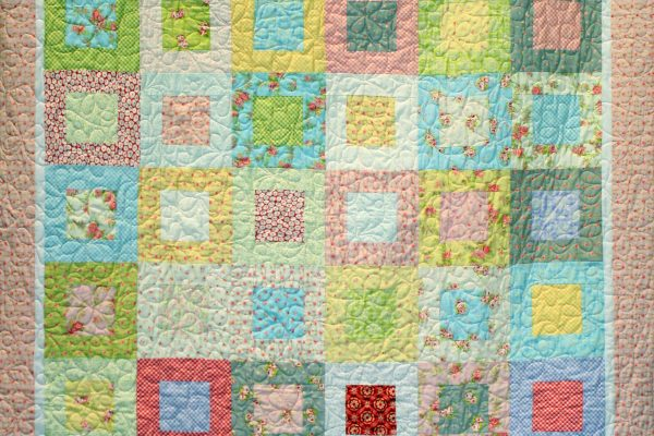 "1st Place - ""Square in a Square"" made by Malorie McIntosh; quilted by Kathy Reynolds on a track mounted machine."