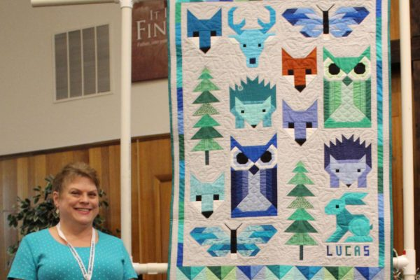 "Gail Vaughan made ""Forest Friends"" from a pattern by Elizabeth Hartman.  She substituted 2 blocks (the bunny and the deer) w/ designs by Lorna McMahan of Sew Fresh Quilts.  The trees are her own design.  She quilted it with leaves and flowers for her niece's new baby boy."