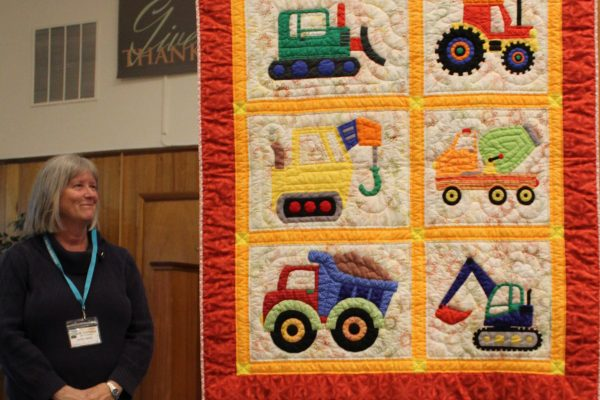 "Kathy made this quilt for her newest grandson, Paul Donovan Schloss.   She teased his brother for months that the baby's name was going to be Bartholomew.  It is machine appliqued and hand quilted.  The pattern is ""I love Dirt."""